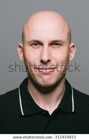 Young man bald portrait on gray background - stock photo
