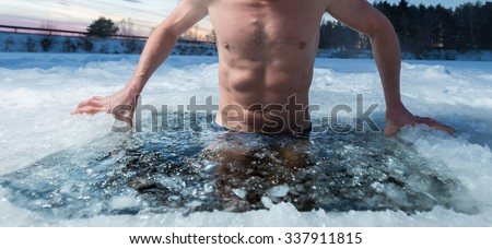 Young man bathing in the ice hole. Focus on the ice in a water only - stock photo