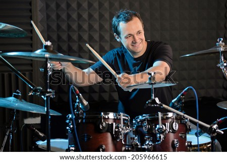 Young man behind drum-type installation in a professional recording studio - stock photo