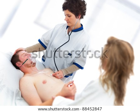 Young man being checked by a doctor for vital signs - stock photo