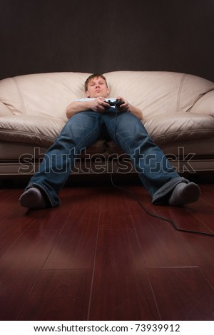 young man being lazy while playing video games on gray background - stock photo