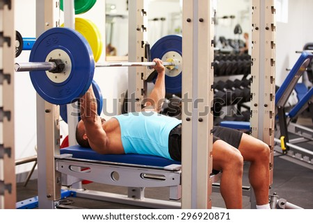 Young man bench pressing weights at a gym, side view - stock photo