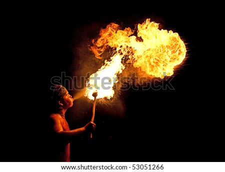 Young man blowing fire from his mouth - stock photo