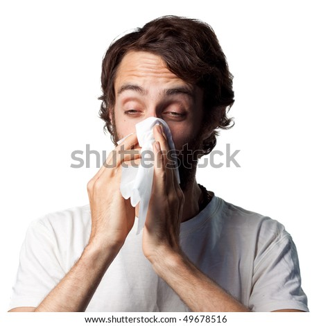 Young man blowing his nose - stock photo