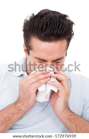 Young Man Blowing His Nose In A Tissue Over White Background - stock photo