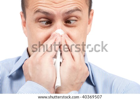 Young man blowing nose, isolated on white background - stock photo