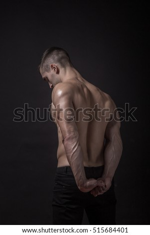 young man bodybuilder ripped, back, rear view. black background, studio.