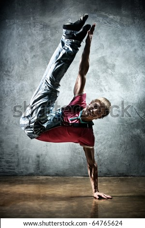 Young man break dance. On wall background.