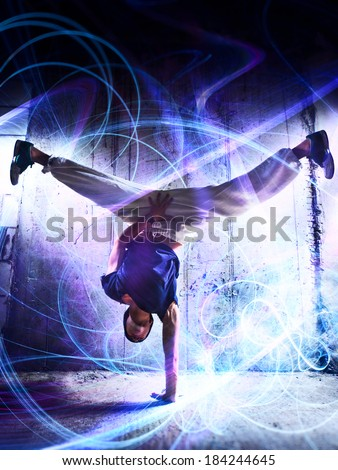 Young man break dance on wall background. With light effects. - stock photo