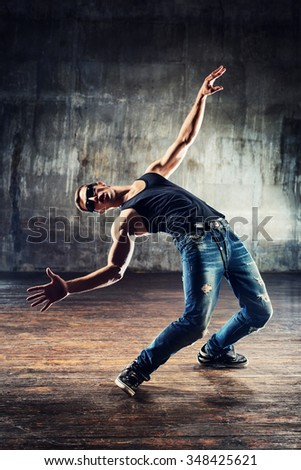 Young man break dancer standing in dodge bullets pose on old wall background - stock photo