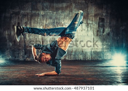 Young man break dancing on old wall background