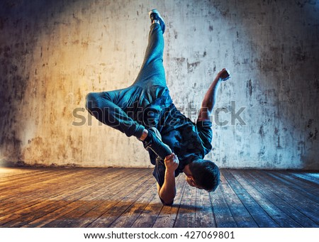 Young man break dancing on wall background. Blue and red lights effect. - stock photo