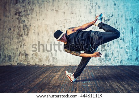Young man break dancing on wall background. Tattoo on body.
