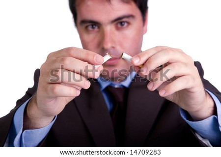 Young man breaking cigarette isolated on white - focus on the cigarette - stock photo