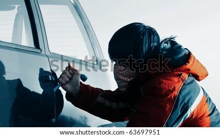 Young man breaking door of a car - stock photo