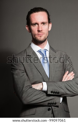 Young man brown long hair with expressive face wearing grey suit and blue tie. Isolated on grey background. - stock photo
