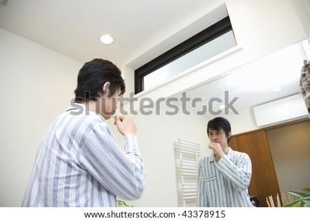 Young man brushing his teeth - stock photo