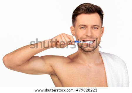 Young man brushing his teeth / Man brushing teeth isolated on white