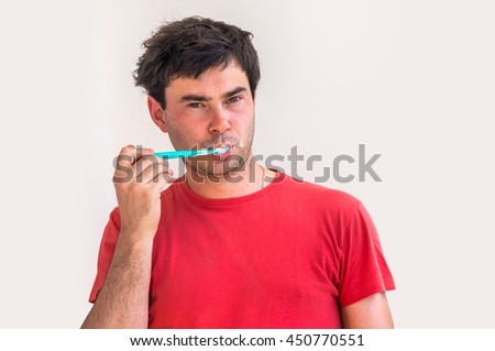 Young man brushing teeth in the morning - dental hygiene