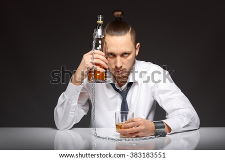 Young man businessman drinking whiskey with a feeling of despair. Addicted to alcohol, alcoholism concept, social problem - stock photo