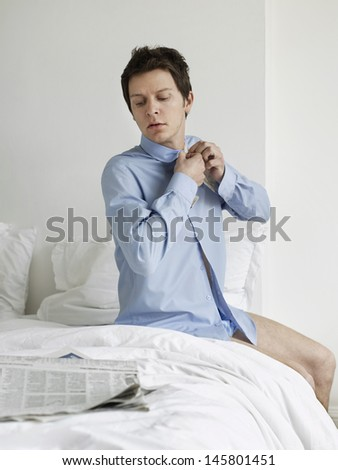 Young man buttoning his shirt while reading newspaper on bed - stock photo