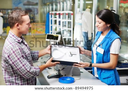 Young man buying business shirt with shop assisant at cash desk in store - stock photo