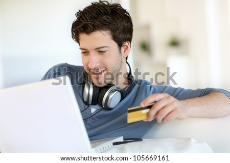 Young man buying music on internet with tablet - stock photo