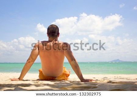 Young man by the sea shore looking at sea, thoughtful. - stock photo