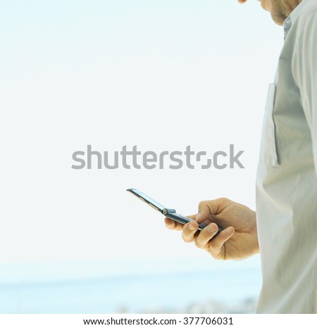 young man call by his smart phone at beach