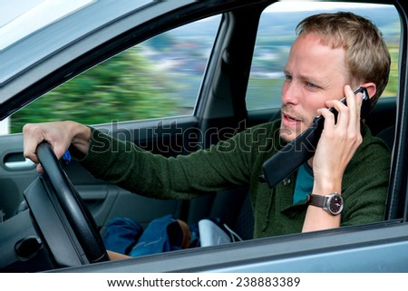 young man calling in the car and is driving