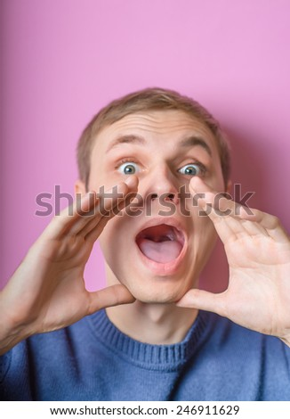 Young man calling, screaming. Gesture. On a purple background. - stock photo