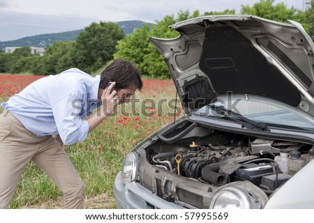 young man calling the car service after a vehicle breakdown - stock photo