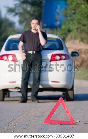 Young man calls to a service standing by a white car. Focus is on the red triangle sign - stock photo