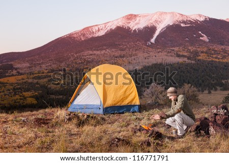 Young Man Camping and Keeping Warm by Fire - stock photo