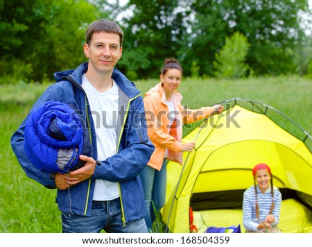 Young man camping near tent in the park - stock photo