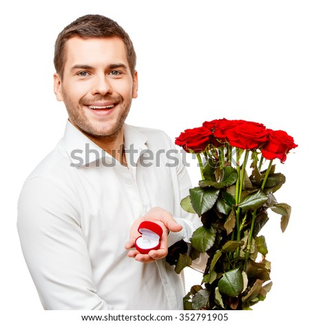 Young man carries heart shaped box and flowers, isolated on white