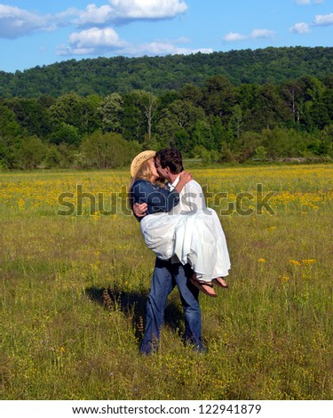 Young man carries wife across flower filled field.  He kisses her as she clings to his shoulders.  She is wearing a denim jacket and cowboy hat. - stock photo