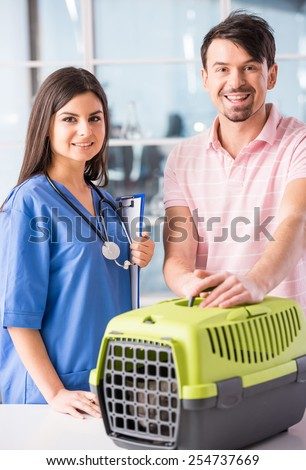 Young man carrying a cat in a box to a veterinarian. - stock photo