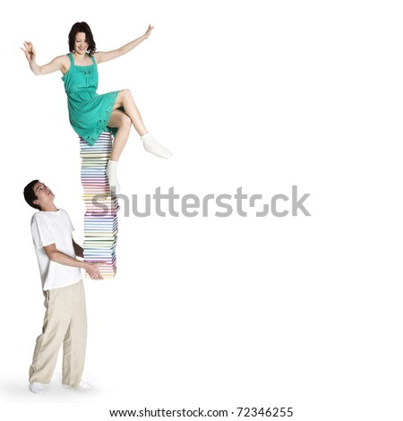 Young man carrying a high stack of colorful books with girl sitting on top of it trying to balance, isolated on white background. - stock photo
