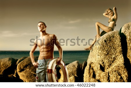 Young man carrying a lifesaver and beautiful woman sitting on a rock looking over the sea - stock photo