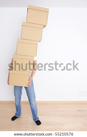 Young man carrying a stack of boxes - stock photo