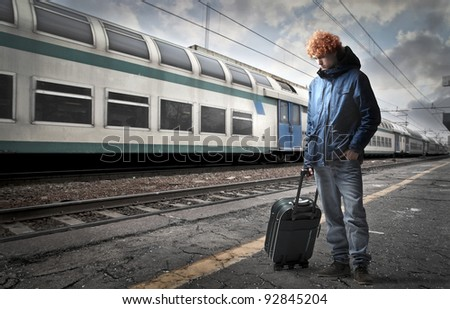 Young man carrying a trolley case on the platform of a train station - stock photo