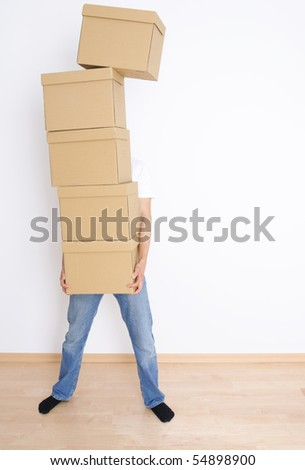 Young man carrying and dropping his stack of moving boxes - stock photo