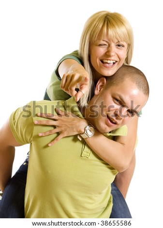 Young man carrying his cute girl on back. woman winking and pointing to you