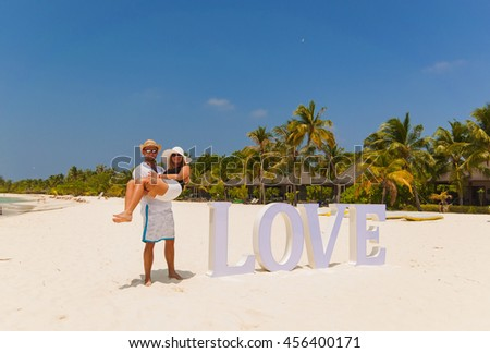 Young man carrying his girlfriend in his arms at the beach - stock photo