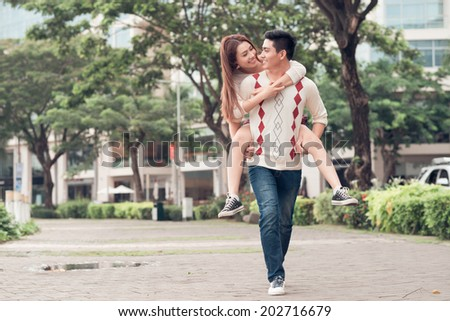 Young man carrying his girlfriend on the back in the park - stock photo