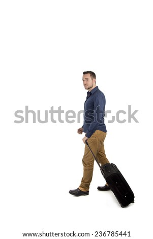 Young man carrying his suitcase while walking against a white background - stock photo