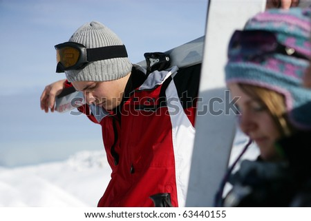 Young man carrying skis - stock photo