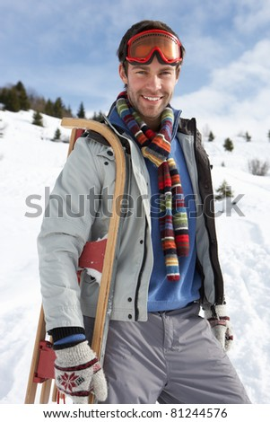 Young Man Carrying Sled In Alpine Landscape - stock photo