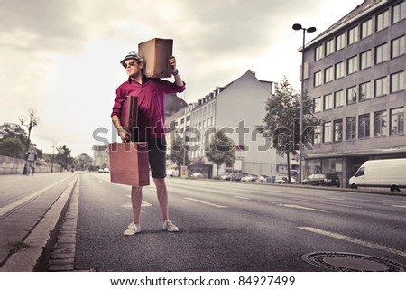 Young man carrying some suitcases on a city street - stock photo